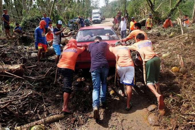 Công nhân Philippines đẩy xe mắc kẹt ở thị trấn Matnog, tỉnh Sorsogon hôm 15-12. Ảnh: EPA