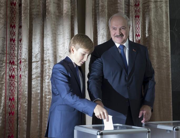 Tổng thống Belarus Alexander Lukashenko cùng con trai tham gia bỏ phiếu trong cuộc bầu cử hôm 11-10. Ảnh: Reuters