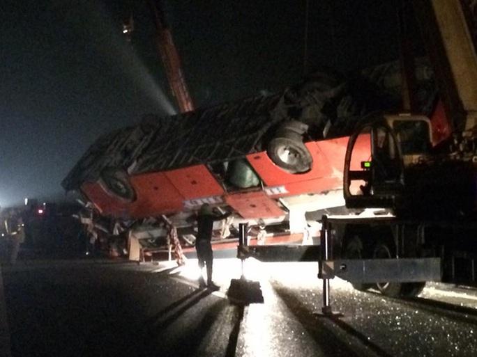 Lực lượng cứu hộ cẩu chiếc xe khách giường nằm lên mặt đường cao tốc
