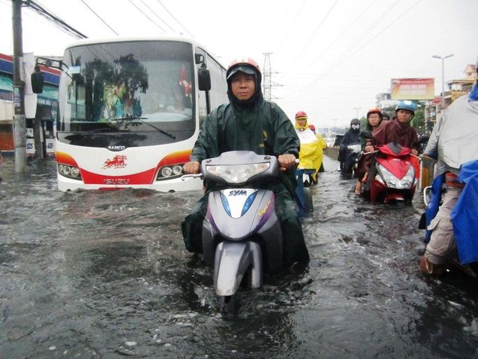 Người dân khốn khổ bì bõm lội nước để về nhà trong giờ tan tầm