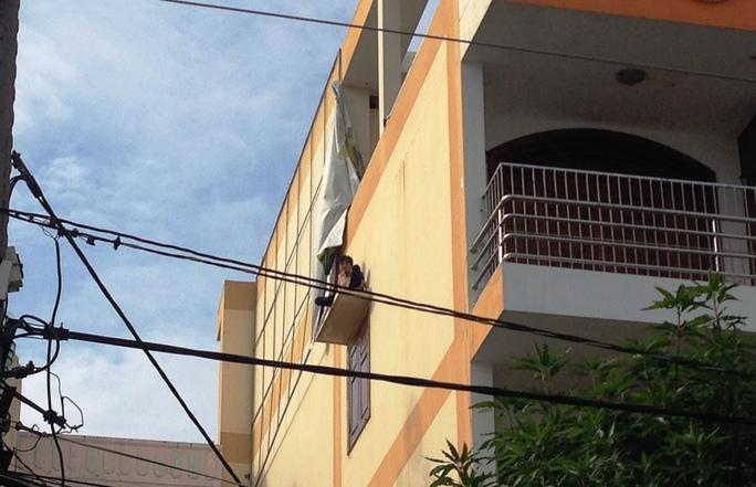 Người thanh niên ngồi vắt vẻo trên tấm đan cửa sổ nhà trẻ lúc sáng sớm
