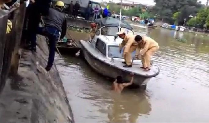 Lực lượng chức năng tìm cách đưa nam thanh niên lên bờ