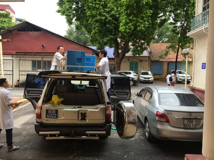 Nhóm giáo sư, bác sĩ, điều dưỡng BV Việt Đức cùng  2 thùng đựng sẵn đá và dung dịch bảo quản tạng từ BV chuẩn bị ra sân bay vào TP HCM nhận tạng hiến
