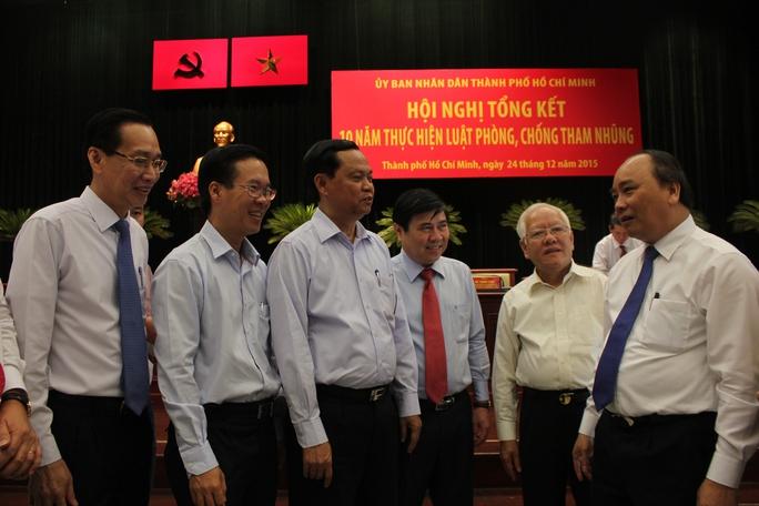 Phó Thủ tướng Nguyễn Xuân Phúc (bìa phải) trao đổi với các đại biểu tại hội nghị.