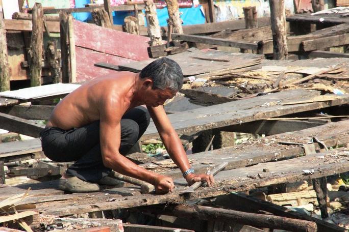 Một người dân đang tháo dỡ từ những căn nhà đã đập phá, dừi đi để lấy vật liệu dựng lại chòi của mình.