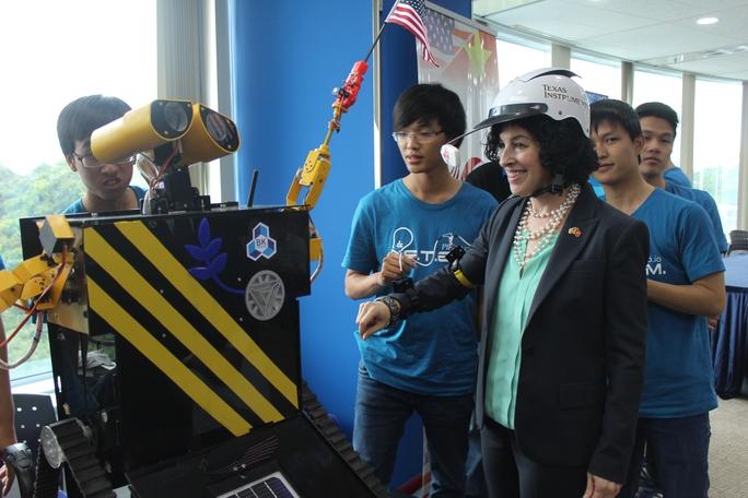 Tổng Lãnh sự Mỹ tại TPHCM Rena Bitter đang thử điều khiển robot do các bạn trẻ Việt Nam trong CLB Robotics chế tạo. Ảnh: Thu Hằng
