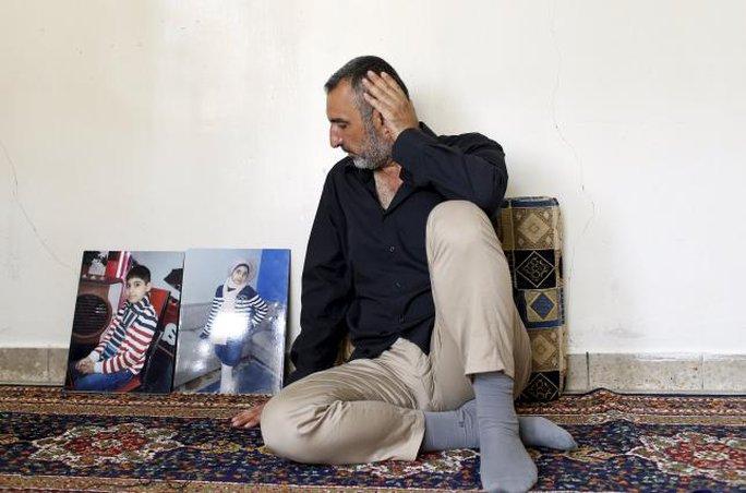 Ông Ahmed Hadi Jawwad ngồi cạnh bức ảnh của hai đứa con  trong cuộc phỏng vấn hôm 11-9 ở Baghdad. Ảnh: REUTERS