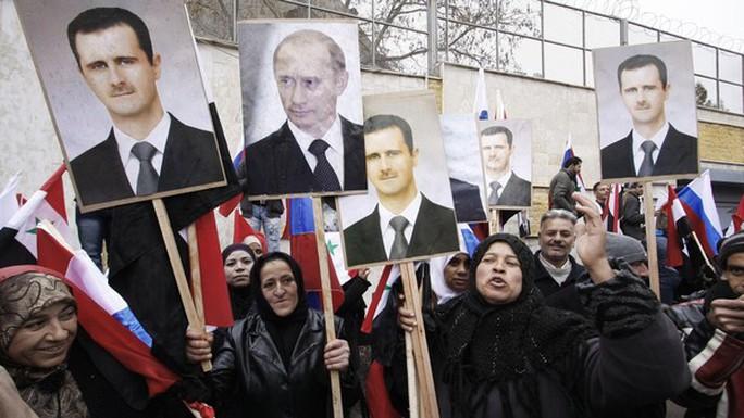 Những người biểu tình ủng hộ chính quyền Syria giơ cao hình ảnh của hai nhà lãnh đạo Bashar al-Assad và Vladimir Putin bên ngoài đại sứ quán Nga tại Damascus. Ảnh: AP