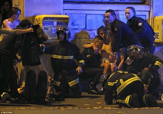 Giải cứu người bị thương gần nhà hát Bataclan. Ảnh: REUTERS