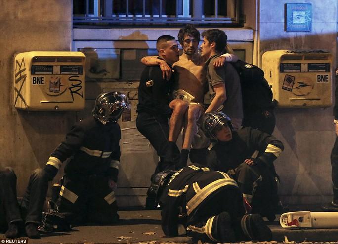 Lực lượng cứu hỏa giải cứu người bị thương gần nhà hát Bataclan Ảnh: REUTERS