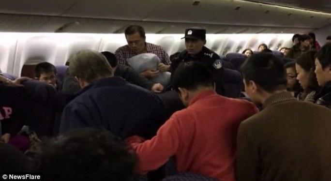 Hành khách khách giúp buộc tay ông này lại. Ảnh: NEWSFLARE