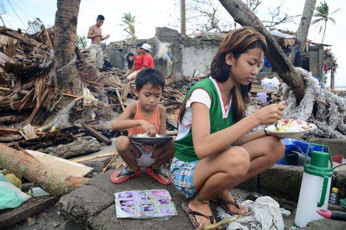 Người dân Philippines ăn uống bên ngoài những căn nhà đổ nát ở tỉnh Sorsogon,miền trung Philippines hôm 15-12. Ảnh: REUTERS
