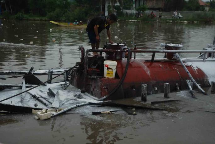 Lực lượng cứu hộ tiến hành hút dầu ra khỏi bồn, tránh để tràn ra môi trường