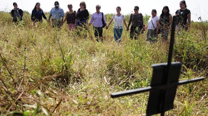 Người thân của những người mất tích tại một ngôi mộ được tin là nơi chôn khoảng 150 thi thể nạn nhân của bọn tội phạm ở gần thị trấn Tetelcingo, bang Morelos hôm 6-11. Ảnh: AP