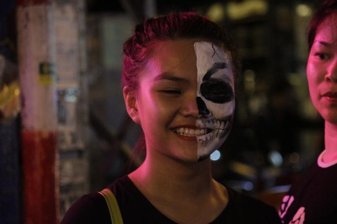 Một cô gái xinh đẹp thích thú với gương mặt vừa được hóa trang độc đáo.