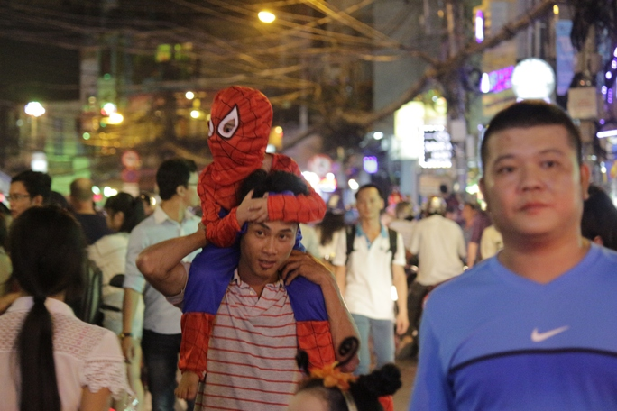 Người nhện tí hon ngồi trên cổ cho bố cõng đi chơi trên đường Bùi Viện.