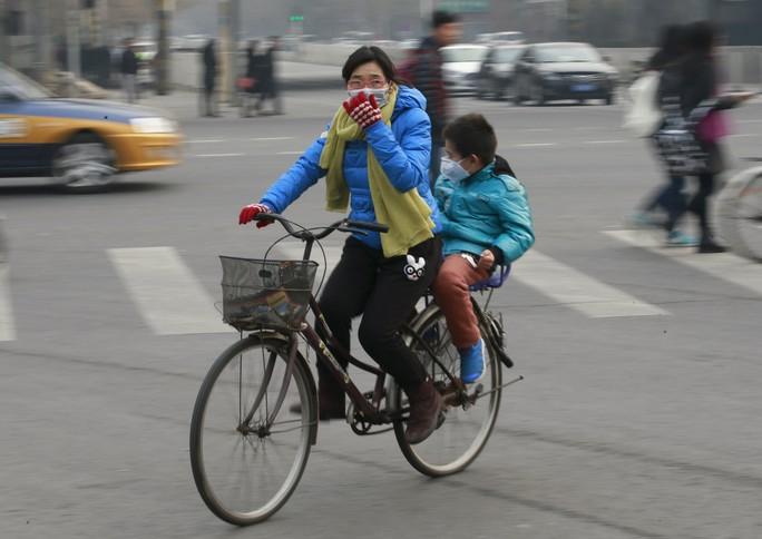 Người dân tại thủ đô Bắc Kinh - Trung Quốc đeo khẩu trang khi ra đường phố hôm 20-12 Ảnh: Reuters