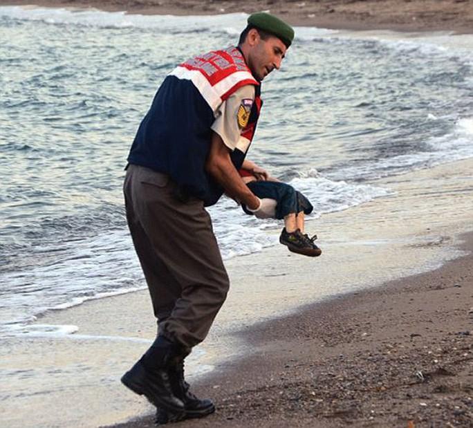 Cậu bé Aylan được cảnh sát Thổ Nhĩ Kỳ đưa đi. Ảnh: Reuters