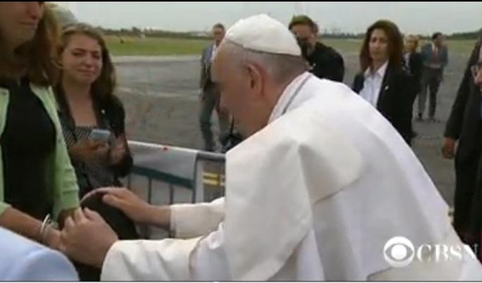 Giáo hoàng cúi xuống hôn và xoa đầu cậu bé.