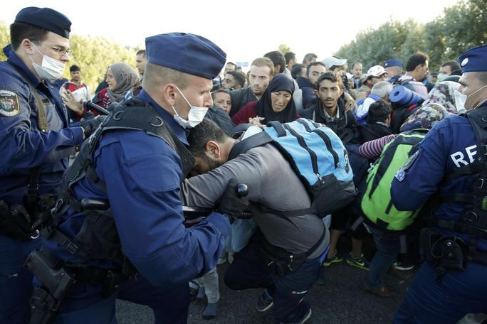 Cảnh sát Hungary xô xát với người di cư ở làng Roszke hôm 7-9 Ảnh: REUTERS