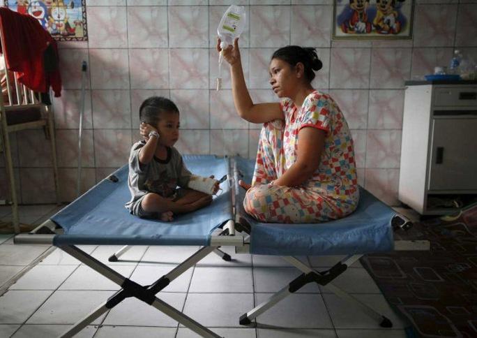Một phụ nữ chăm sóc con trai mắc bệnh hô hấp do bụi mù tại tỉnh Trung Kalimantan - Indonesia Ảnh: Reuters
