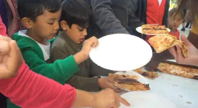 Những người nhập cư nhận bánh pizza. Ảnh: NBC News