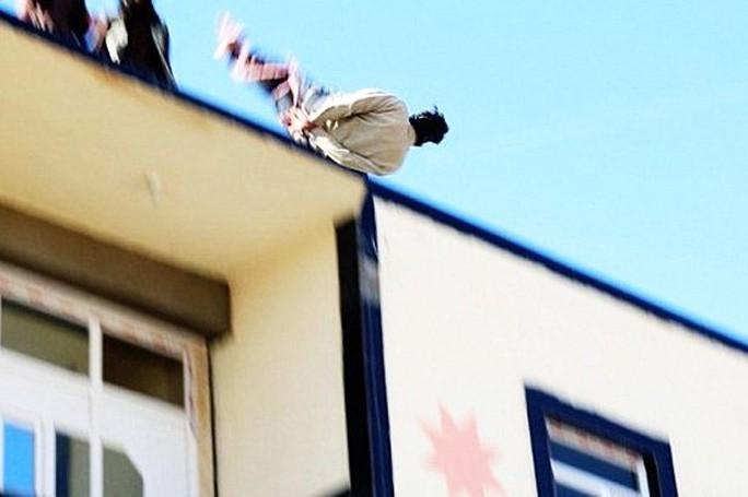 IS đẩy người đồng tính từ mái nhà xuống đất. Ảnh: Mirror