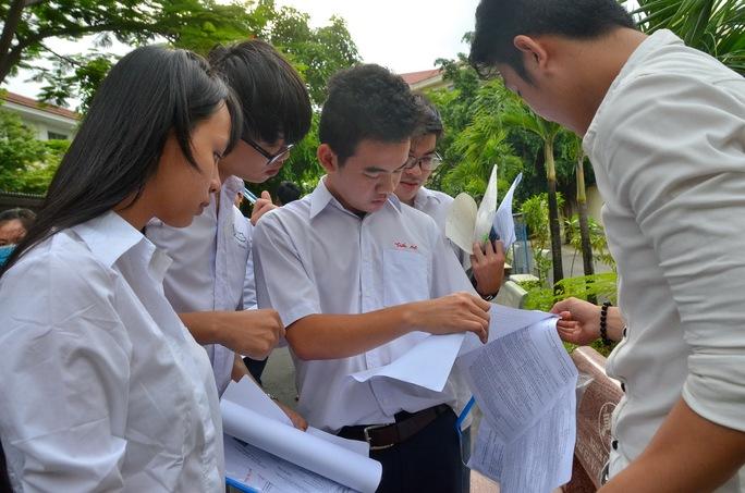Thí sinh xem lại đề thi môn vật lý tại Trường THPT Trần Quang Khải. Ảnh: Tấn Thạnh