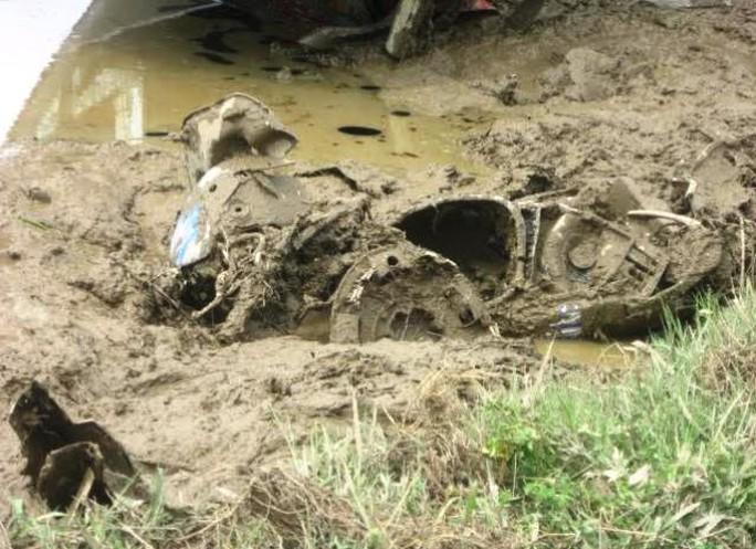Chiếc xe máy hư hỏng nặng nằm sâu dưới ruộng lúa mới cấy do bị xe ô tô đè lên
