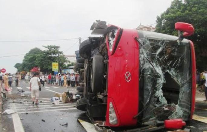 Chiếc xe khách lật nghiêng, kính xe vỡ nát nằm chắn ngang quốc lộ 1A