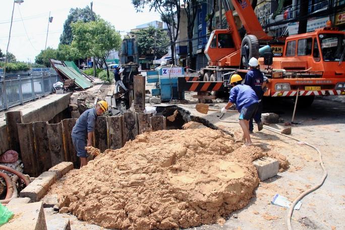 Lòng hố có chiều sâu khoảng 5 m vẫn còn đọng nước, đang được công nhân lấp đất.