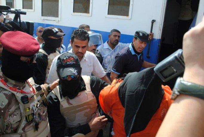 Một tử tội IS bị lực lượng an ninh áp giải tại nhà tù thuộc TP Nasiriya hôm 21-8. Ảnh: REUTERS