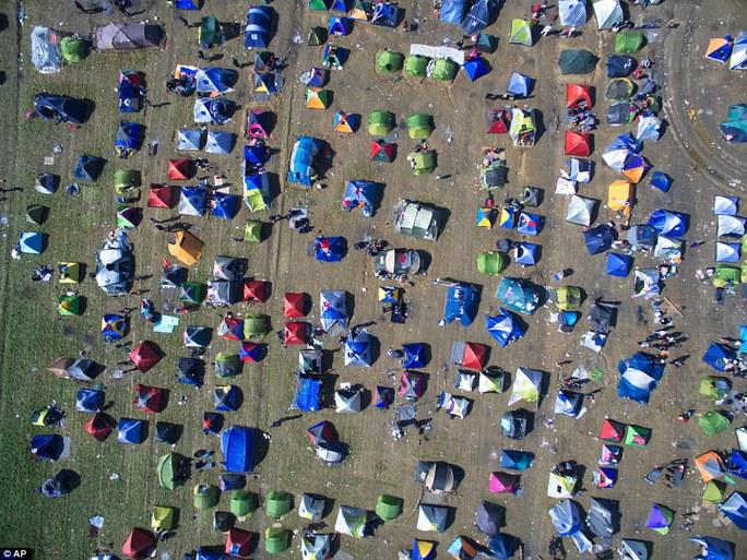 Ít nhất 10 ngàn người tị nạn, trong đó có không ít trẻ em, đã sống trong những lều tạm này nhiều ngày qua với điều kiện thiếu thốn cùng cực và mỗi ngày lại có hàng trăm người tới thêm. Tình trạng này xảy ra khi giới chức Macedonia thiết lập hệ thống hàng rào thép gai để kiểm soát dòng di chuyển của người di cư. Ảnh: AP