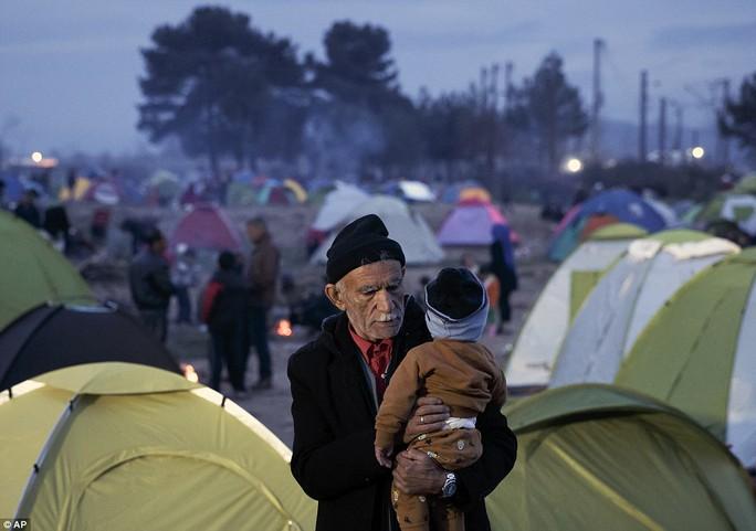 Cụ ông bế đứa cháu nhỏ tại Idomeni giữa bộn bề những chiếc lều tị nạn sau lưng. Ảnh: AP