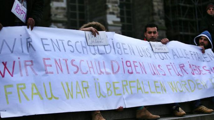 Người di cư từ Ai Cập và Morocco giăng banner ở nhà ga Cologne để gởi lời xin lỗi tới những phụ nữ là nạn nhân của vụ bạo lực đêm Giao thừa. Ảnh: EPA