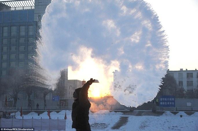 Nước đóng băng ngay khi vừa được vẩy lên trời. Ảnh: Tân Hoa Xã