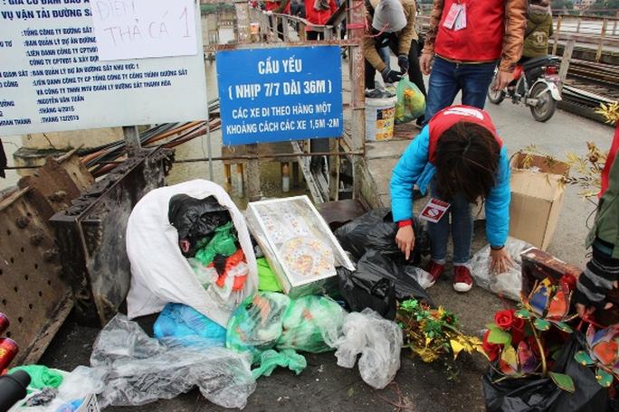 Phía đầu cầu, một tổ túc trực tại đây thu gom rác