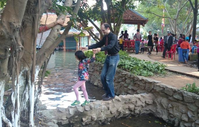 Một khách nước ngoài trải nghiệm cảm giác qua suối cùng con gái