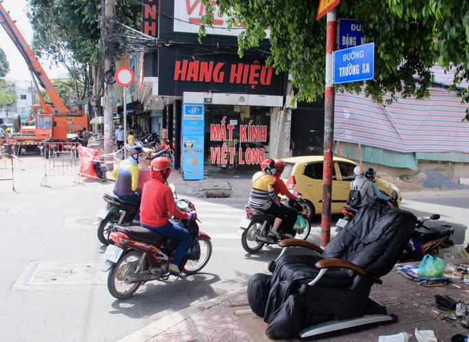 Các phương tiện lưu thông vào đường Đặng Văn Ngữ rồi vòng ra đường Trường Sa trong thời gian hiện trường vụ sụt lún đang được xử lý