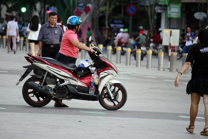 Nhiều người dắt xe máy, thậm chí chạy xe máy ngang phố đi bộ Nguyễn Huệ bất chấp biển báo cấm.