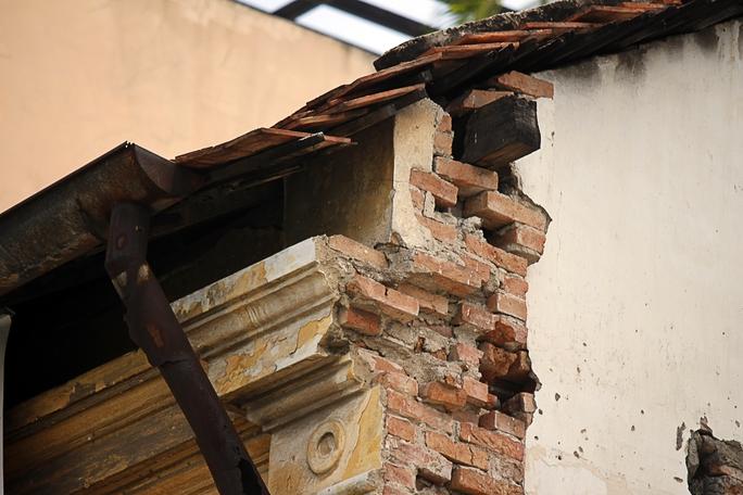 Một phần mái nhà đã lung lay, nứt từng mảng lớn, gạch và tường bị bong tróc rơi xuống đường.