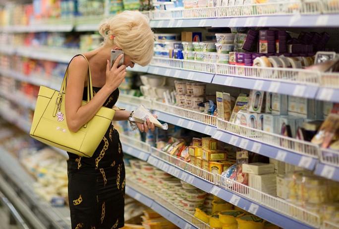 Một người Nga đang dùng điện thoại iPhone tại siêu thị ở thủ đô Moscow - Ảnh: Bloomberg