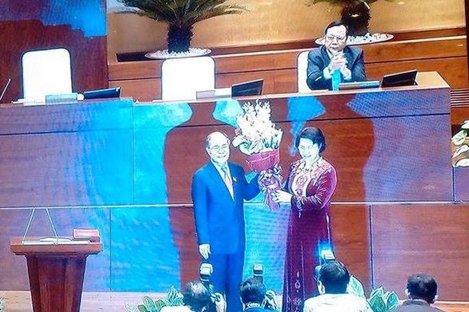 Ông Nguyễn Sinh Hùng tặng và nhận lại bó hoa tươi thắm từ người kế nhiệm - Ảnh chụp qua màn hình
