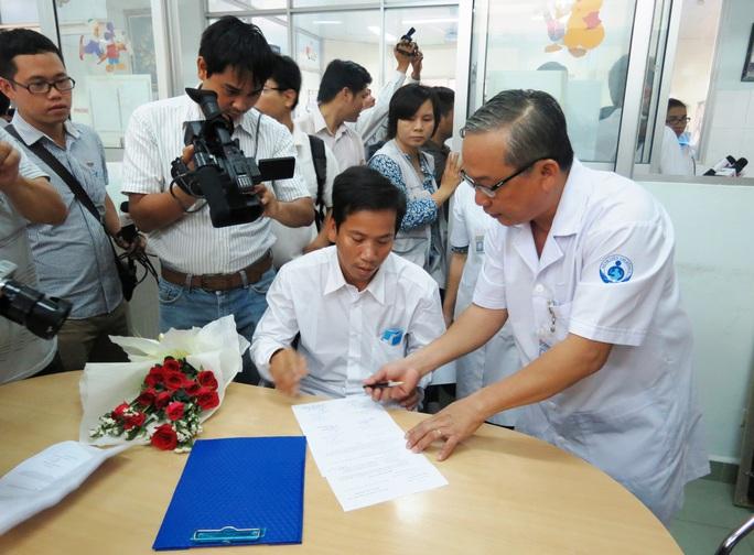 """TS-BS Nguyễn Thanh Hùng, Giám đốc BV Nhi Đồng 1, chuyển giao sổ tiết kiệm 1,29 tỉ đồng và hơn 350 triệu đồng tiền mặt từ các nhà hảo tâm cho cha ruột của cháu bé """"văng khỏi bụng mẹ"""" vào năm 2014 trước sự chứng kiến của chính quyền địa phương và các cơ quan truyền thông"""