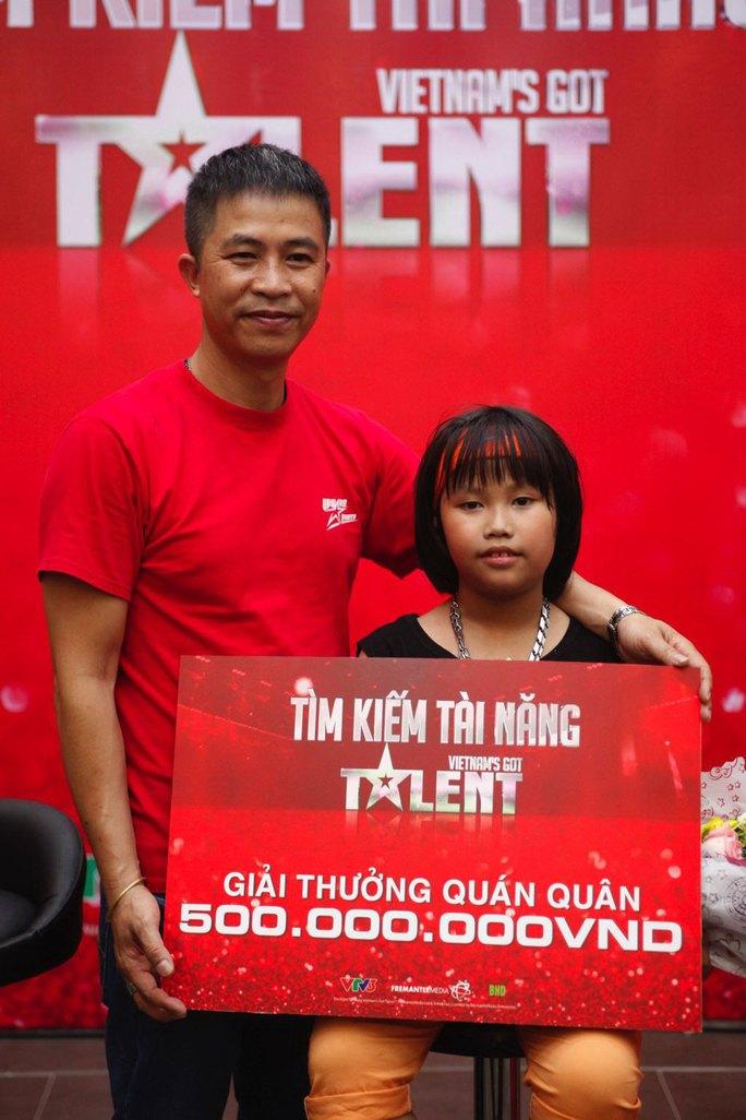 Bé Trọng Nhân chụp ảnh cùng cha sau khi nhận giải Ảnh: ÂN NGUYỄN
