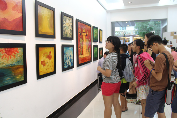 Các em học sinh thích thú xem tranh tại triển lãm. Ảnh Ngọc Lê