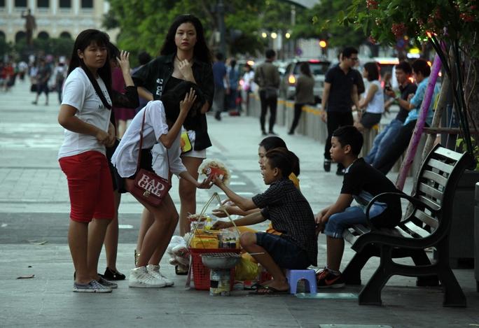 Nhiều người chiếm ghế ngồi ở Phố Đi Bộ làm nơi buôn bán đồ ăn vặt, tấp nập mua bán.