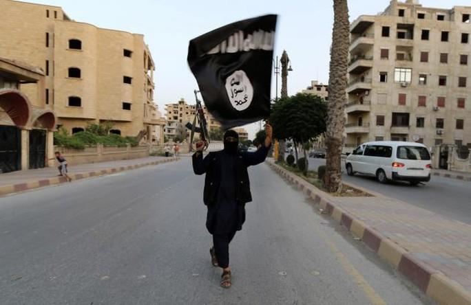 Một phiến quân IS vẫy cờ ở TP Raqqa - Syria. Ảnh: REUTERS