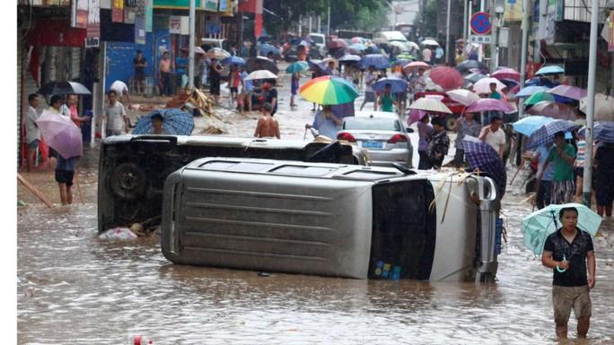 Xe cộ bị lật trong nước lũ ở TP Tô Châu, tỉnh Quảng Tây hôm 14-6. Ảnh: REUTERS