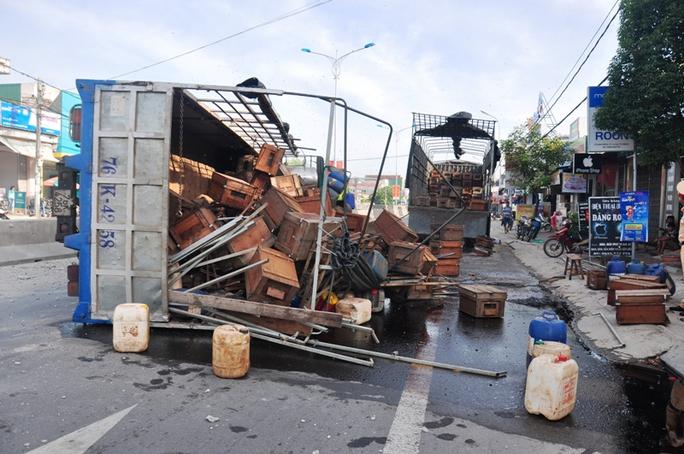 Xe tải chở ong lật nghiêng khiến hàng trăm thùng ong đổ ra đường. Ảnh: T.Trực